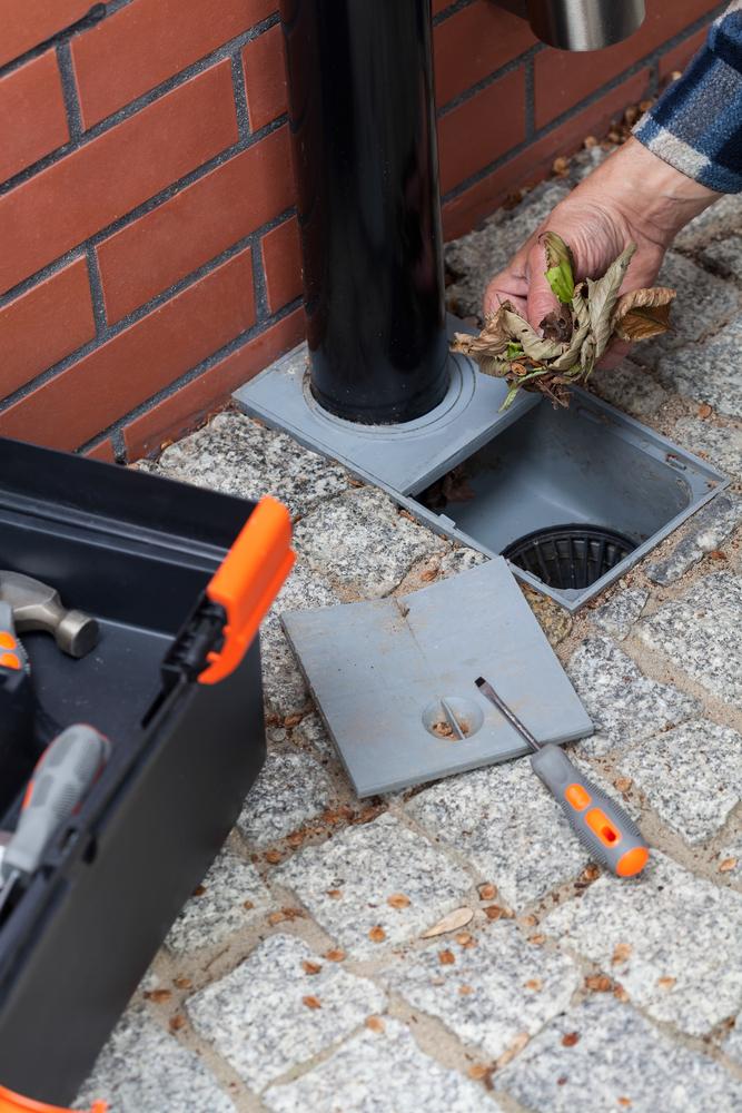 Elderly man cleans the gutter outside